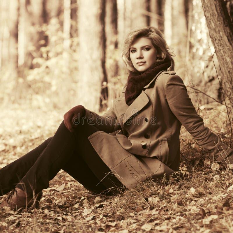 De gelukkige jonge blonde zitting van de maniervrouw op grond in de herfstbos royalty-vrije stock foto's