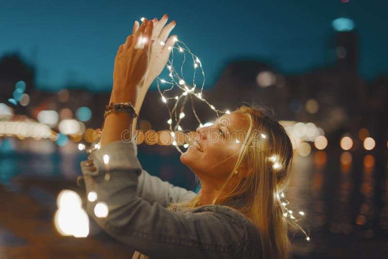 De gelukkige jonge blondevrouw met de lichten van de slingerfee heeft pret in c stock foto