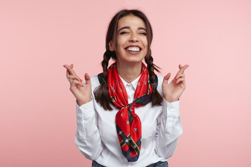 De gelukkige jonge dame heeft grappige blije die uitdrukking, houdt vingers voor goed geluk met gesloten ogen, gekleed in witte o stock afbeeldingen
