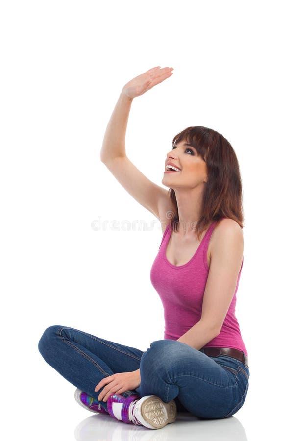 De gelukkige Jonge die Vrouw zit Benen op Vloer worden gekruist, Kijkend Omhooggaande en Golvende Hand royalty-vrije stock afbeeldingen