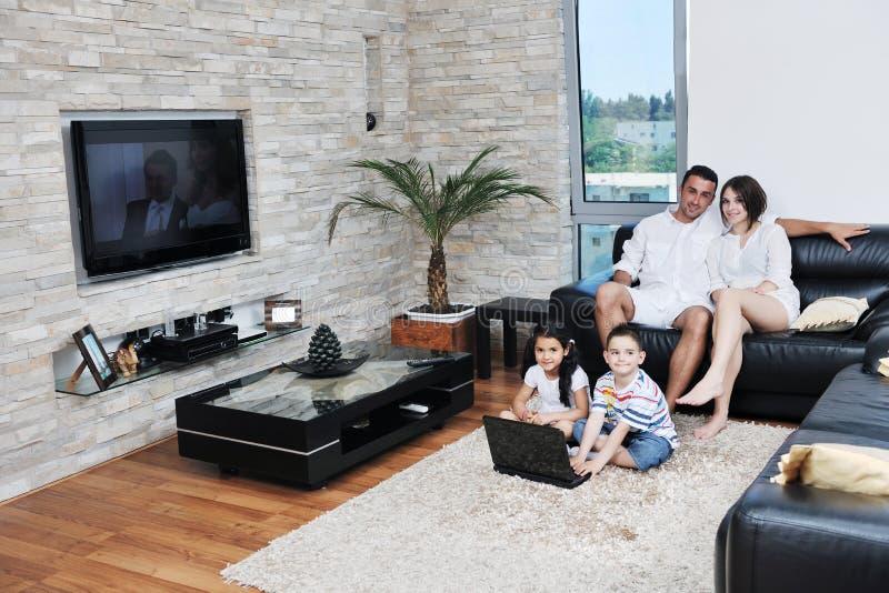 De gelukkige jonge familie heeft een pret thuis met laptop stock afbeeldingen