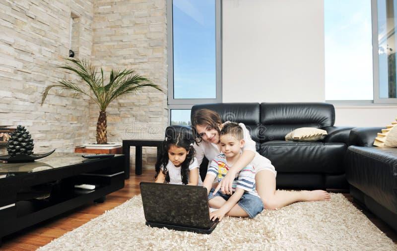 De gelukkige jonge familie heeft een pret thuis met laptop stock foto's