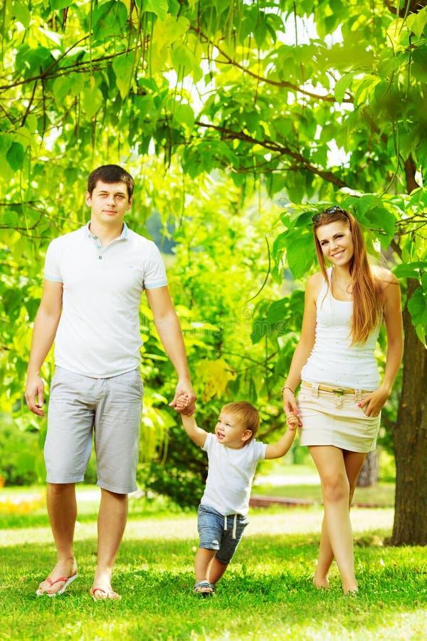 De gelukkige jonge familie heeft pret in groene outdoo van het de zomerpark stock foto