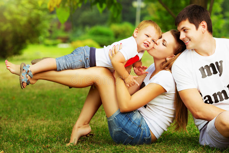 De gelukkige jonge familie heeft pret in groene outdoo van het de zomerpark stock afbeeldingen
