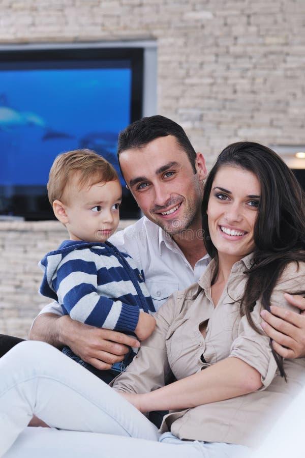 De gelukkige jonge familie heeft pret met TV in backgrund stock afbeeldingen