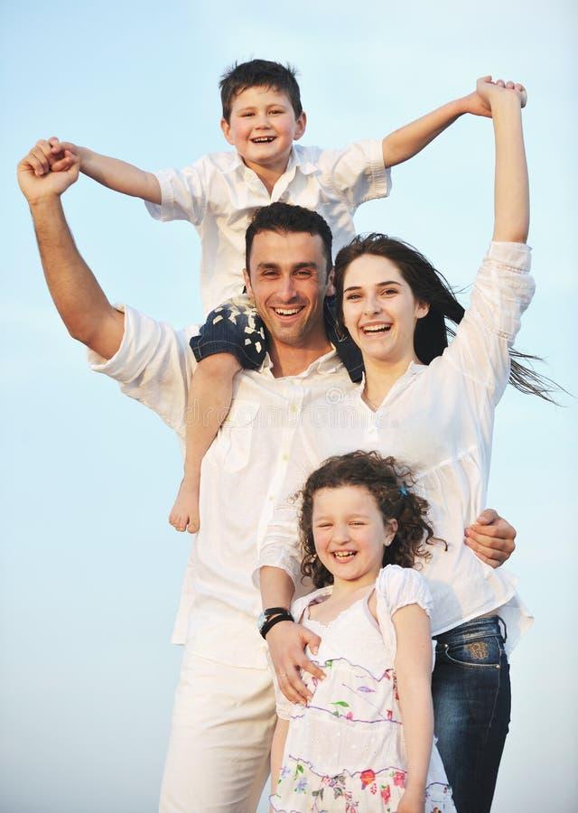 De gelukkige jonge familie heeft pret op strand bij zonsondergang stock fotografie