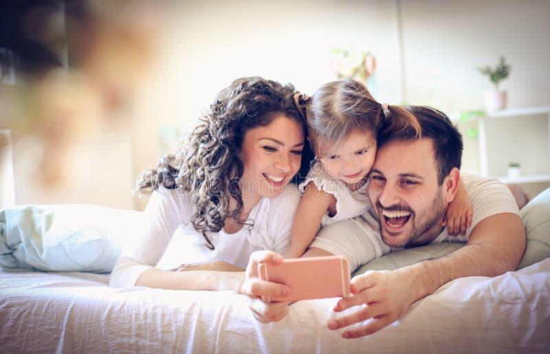 De gelukkige jonge familie neemt een zelfportret met slimme telefoon stock fotografie