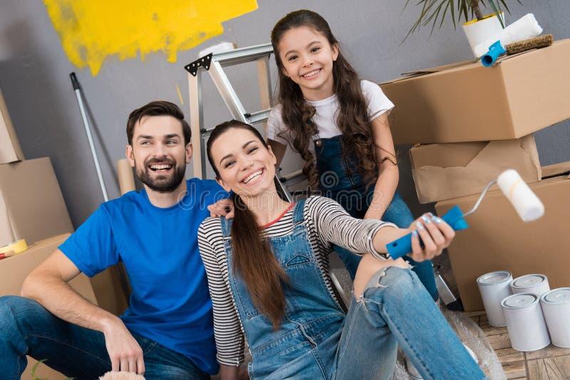 De gelukkige jonge familie ontmantelt kartondozen en maakt het huisverbetering stock afbeeldingen