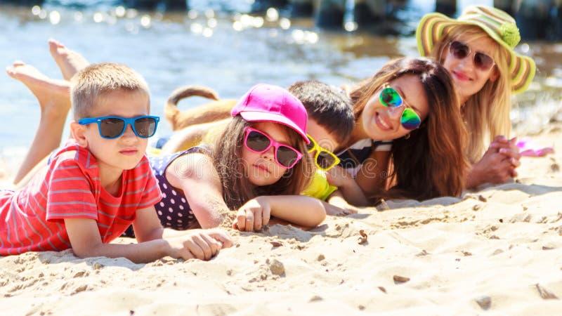 De gelukkige jonge geitjes die van familievrouwen op strand zonnebaden royalty-vrije stock foto's
