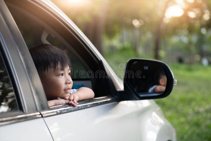 De gelukkige jonge geitjesreis door de auto, Weinig jongen gluurt uit de auto in de zonsondergang stock foto