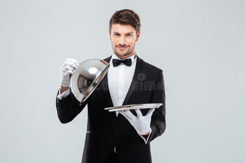 De gelukkige jonge glazen kap van het kelners opheffende metaal van het dienen van dienblad stock foto's