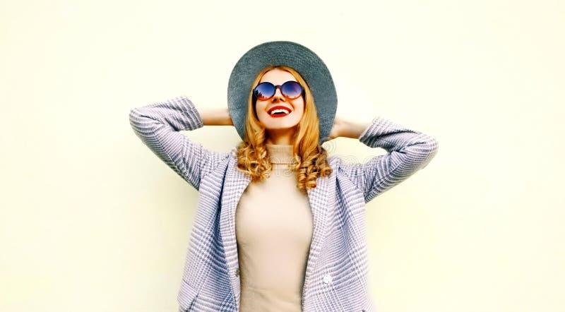 De gelukkige jonge glimlachende vrouw die van het portretclose-up van het leven genieten die roze laag, ronde hoed dragen royalty-vrije stock fotografie