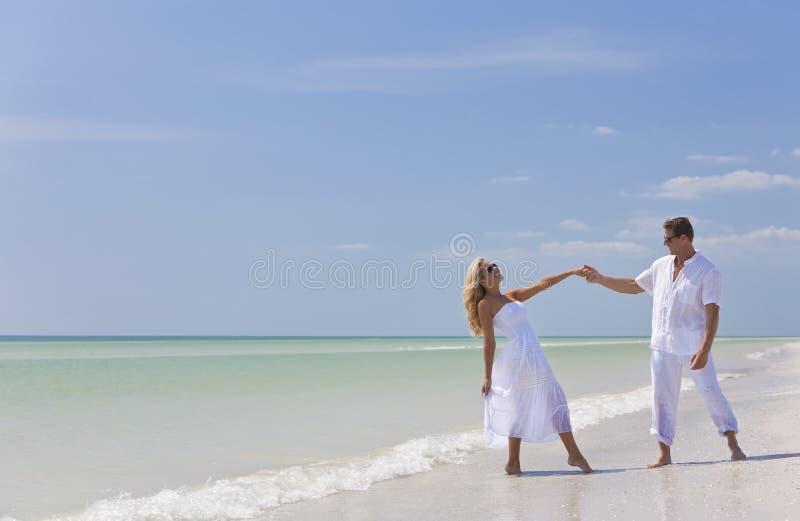 De gelukkige Jonge Handen van de Holding van het Paar Dansende op Strand stock afbeeldingen