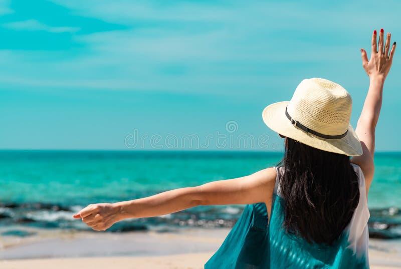 De gelukkige jonge het strohoed van de vrouwenslijtage zit en hief hand bij zandstrand op Ontspannend en geniet van vakantie bij  royalty-vrije stock afbeelding