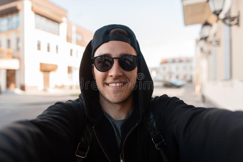 De gelukkige jonge hipstermens in modieuze zonnebril in een zwarte hoodie in een honkbal GLB met een leuke glimlach maakt een sel royalty-vrije stock foto