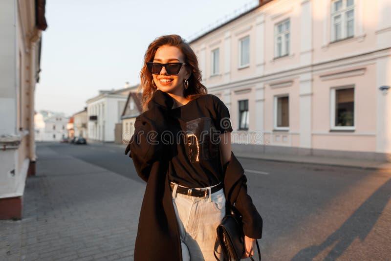 De gelukkige jonge hipstervrouw in in kleren in modieuze zonnebril loopt rond de stad en geniet van de heldere oranje de lentezon royalty-vrije stock foto's