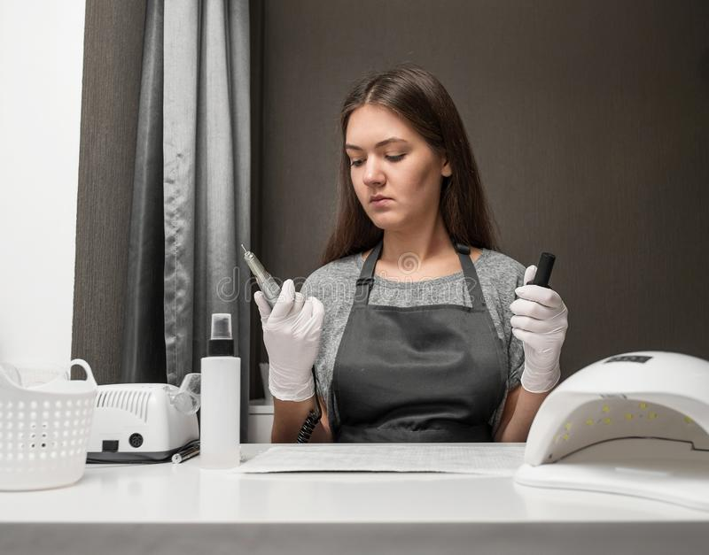 De gelukkige jonge manicure van het vrouwenberoep met schaar en nagellak op grijze achtergrond stock afbeeldingen