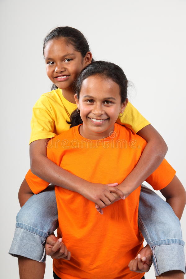 De gelukkige jonge meisjes die van schoolvrienden op de rug geven royalty-vrije stock fotografie