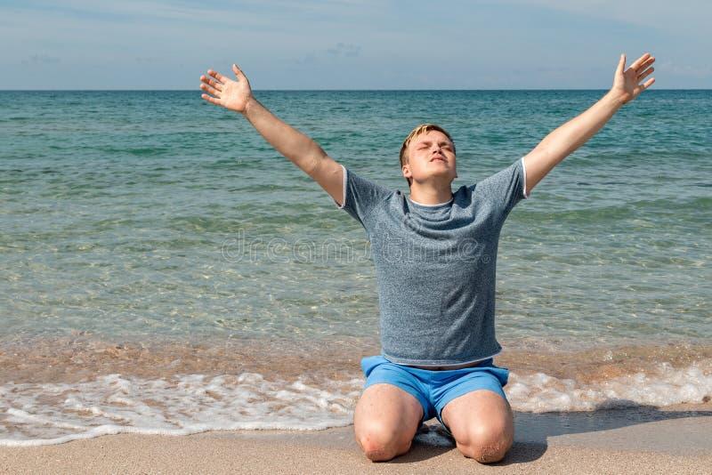 De gelukkige jonge mens in een t-shirtzitting op de kust en bekijkt het overzees, achtermening royalty-vrije stock foto's