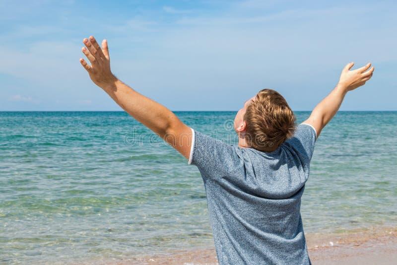 De gelukkige jonge mens in een t-shirtzitting op de kust en bekijkt het overzees, achtermening royalty-vrije stock fotografie