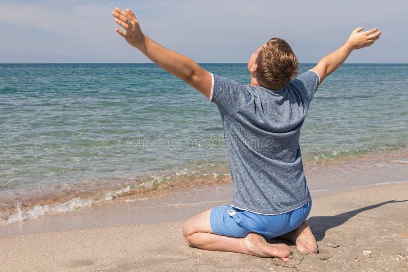 De gelukkige jonge mens in een t-shirtzitting op de kust en bekijkt het overzees, achtermening stock afbeelding