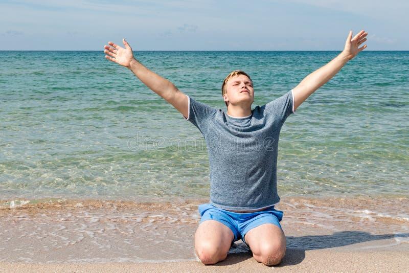 De gelukkige jonge mens in een t-shirtzitting op de kust en bekijkt het overzees, achtermening stock fotografie