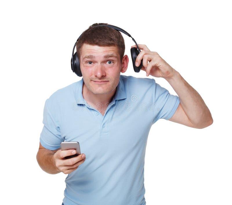 De gelukkige jonge mens met hoofdtelefoons probeert om iemand te horen stock afbeeldingen