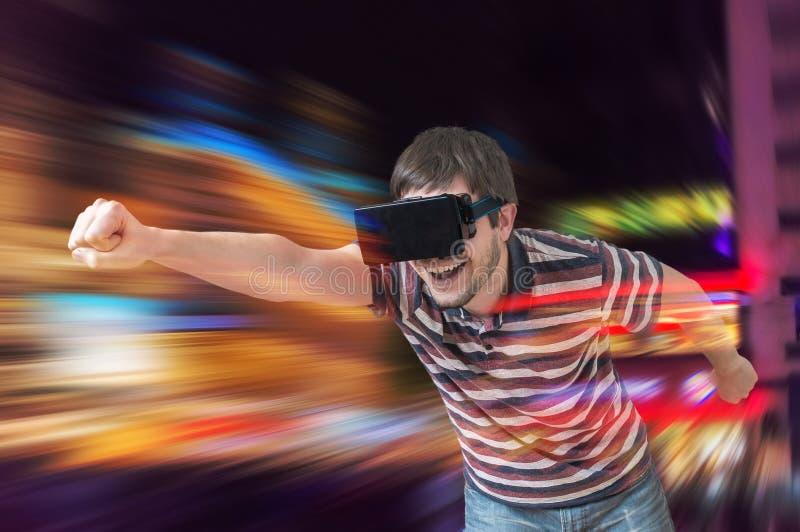 De gelukkige jonge mens speelt het rennen videospelletje in 3D virtuele werkelijkheidssimulator royalty-vrije stock fotografie