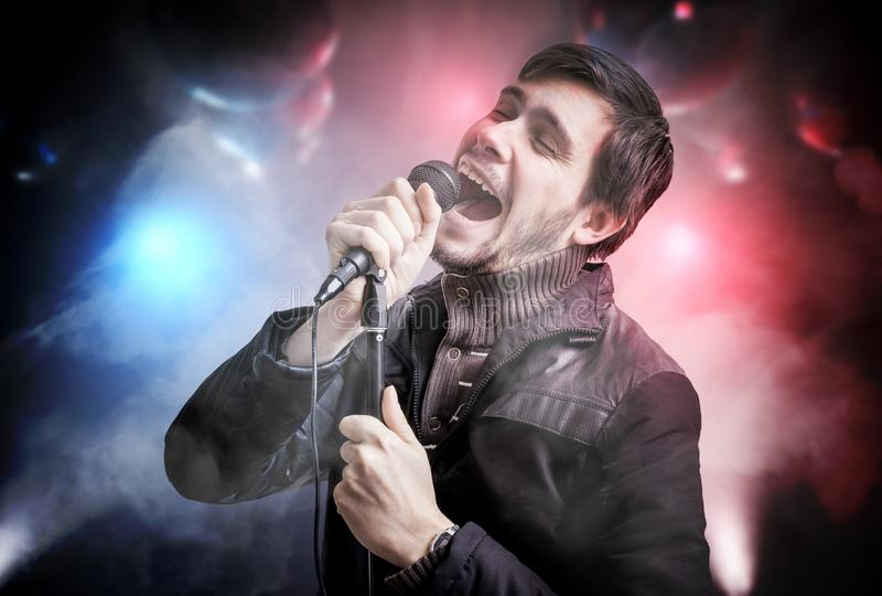 De gelukkige jonge mens zingt lied in discoclub bij nacht royalty-vrije stock foto