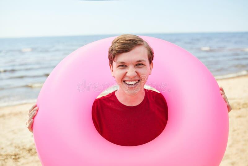 De gelukkige Jonge Mensenholding zwemt buis bij Strand stock foto