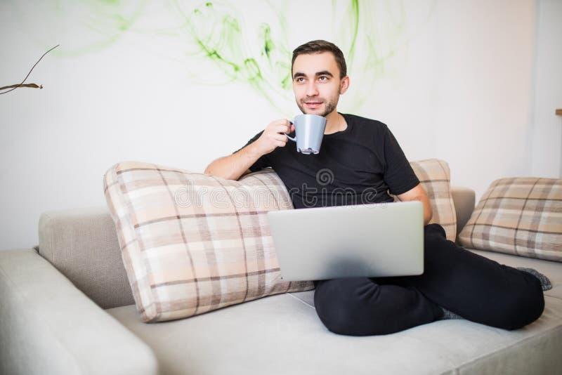 De gelukkige jonge mensenzitting op bank met laptop en hoofdtelefoon en de holding een koffie vormen in zijn hand tot een kom royalty-vrije stock afbeeldingen
