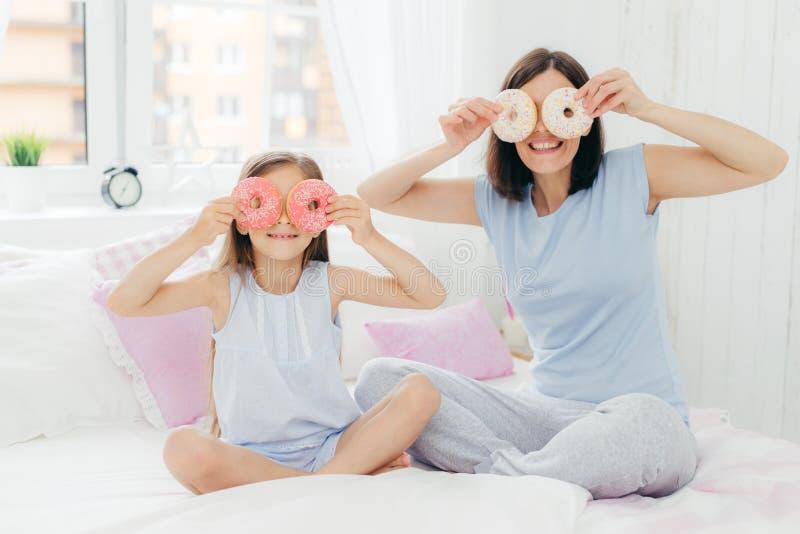 De gelukkige jonge moeder en de dochter hebben pret samen, houden smakelijke zoete doughnuts dichtbij ogen, zitten gekruiste bene stock afbeelding