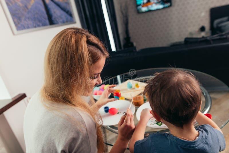 De gelukkige Jonge moeder en haar van Pasen weinig zoon die paaseieren schilderen royalty-vrije stock foto's