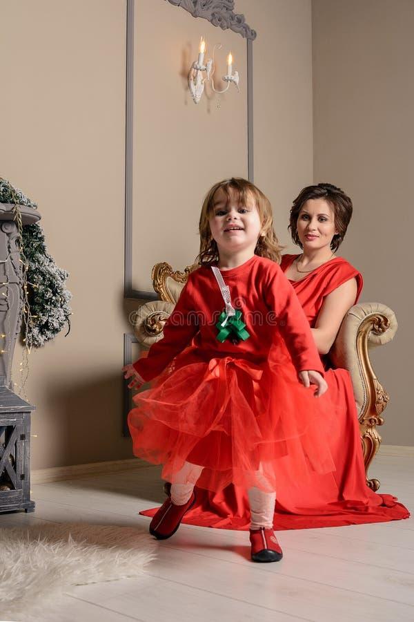 De gelukkige jonge moeder houdt op de handen haar leuk babymeisje op Kerstmis en Nieuw Kind van de jaarvakantie met mamma in rode stock afbeelding