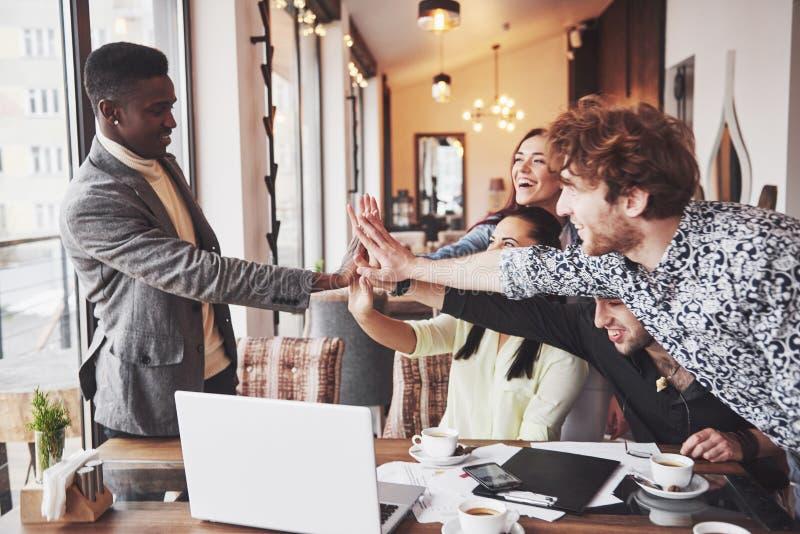 De gelukkige jonge ondernemers in vrijetijdskleding bij koffie dienen of in bedrijfsbureau in die hoge fives geven aan elkaar als royalty-vrije stock afbeelding