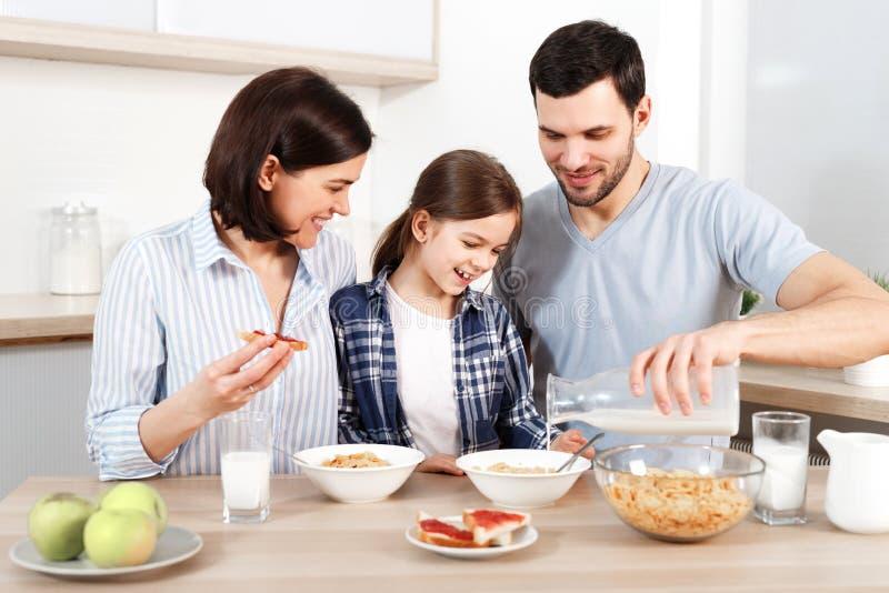 De gelukkige jonge ouders en hun mooie dochter zitten samen bij keukenlijst, eten vlokken, hebben gezond ontbijt, genieten van royalty-vrije stock afbeelding