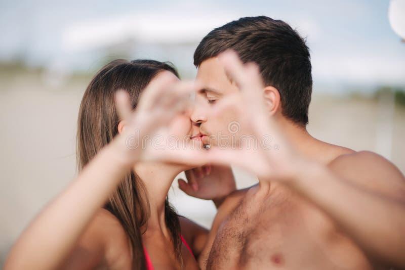 De gelukkige jonge paarkus en maakt een hart door handen Paar dat op het strand loopt Liefde royalty-vrije stock foto