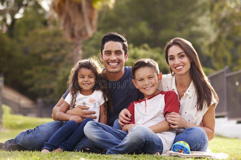 De gelukkige jonge Spaanse familie die het gras in het park zitten die aan camera glimlachen, sluit omhoog stock fotografie