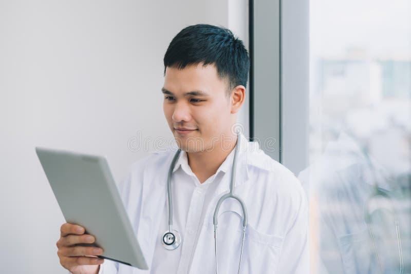 De gelukkige jonge tablet van de artsenholding stock afbeelding