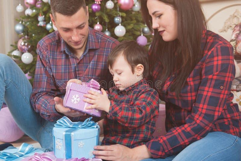 De gelukkige jonge vader en het kind van de familiemoeder met Kerstmisgift B royalty-vrije stock afbeeldingen
