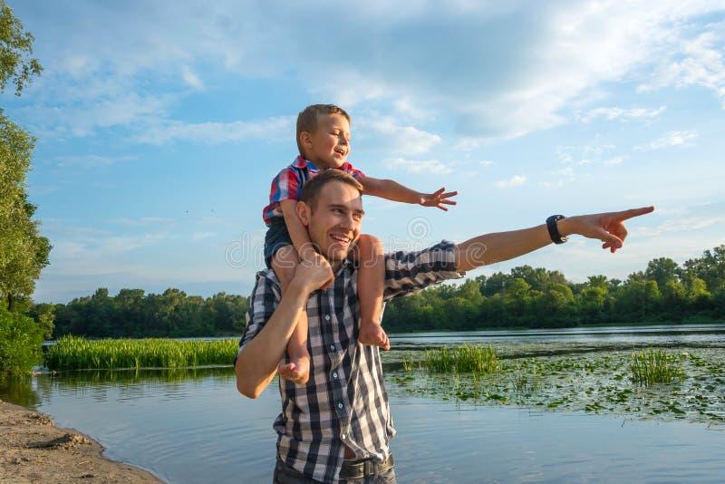 De gelukkige jonge vader houdt zijn rit van het zoonsvervoer per kangoeroewagen op zijn schouders stock fotografie