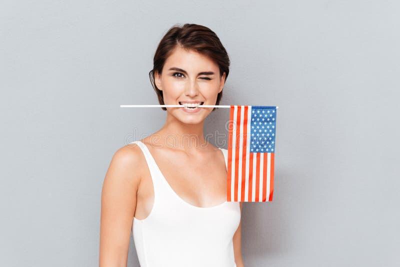 De gelukkige jonge vlag van de V.S. van de vrouwenholding in tanden en het knipogen stock foto's