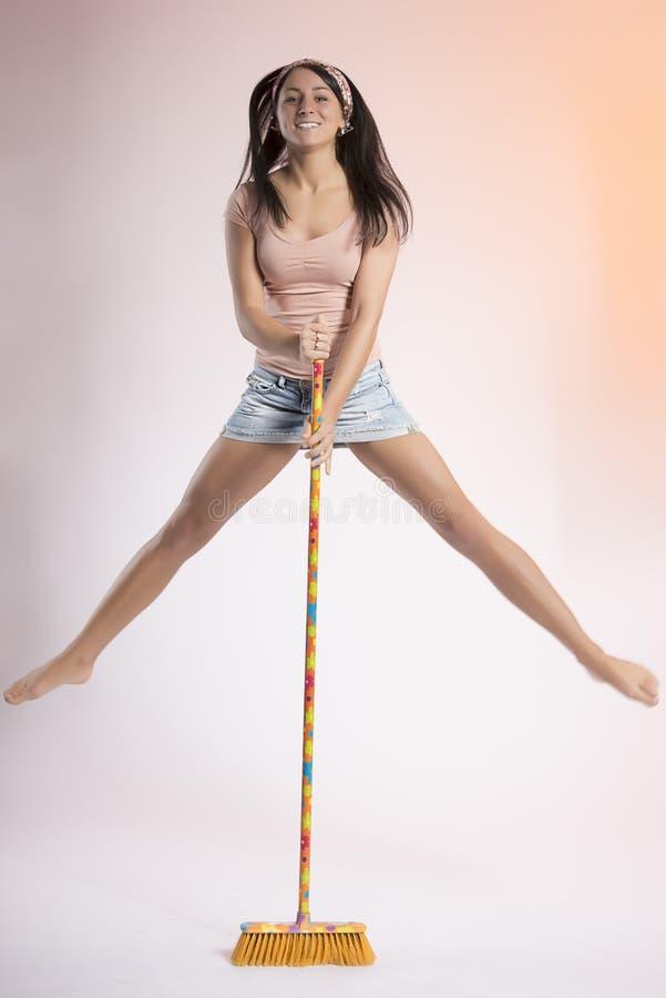 Gelukkig meisje die hoge holdingshanden op een bezem springen stock fotografie