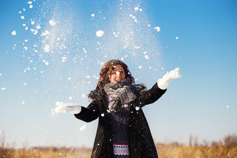 De gelukkige jonge vrouw heeft pret en geniet van verse sneeuw royalty-vrije stock fotografie