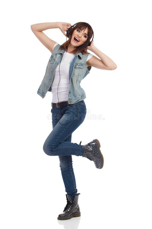 De gelukkige Jonge Vrouw in Hoofdtelefoons danst en zingt stock foto's