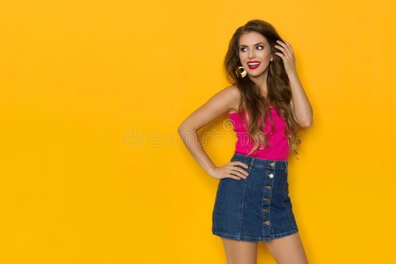 De gelukkige Jonge Vrouw in Jeans Mini Skirt And Pink Top kijkt weg en spreekt stock afbeelding