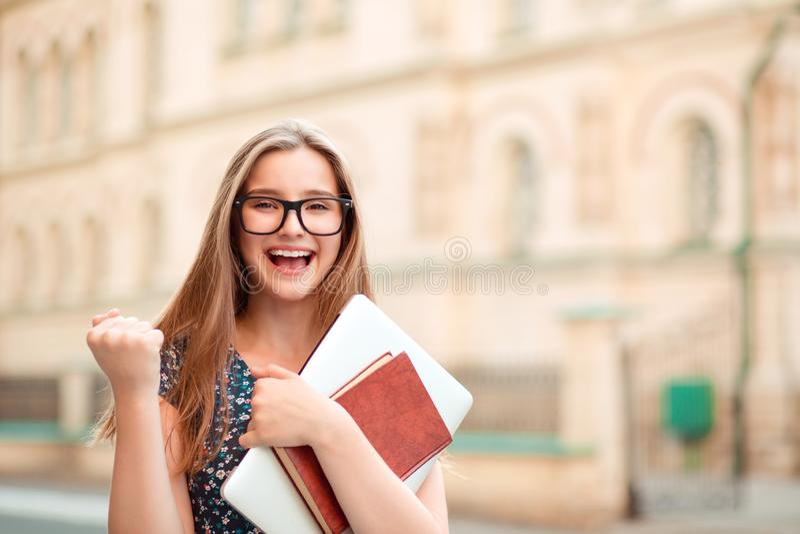 De gelukkige jonge gelukkige vrouw jubelt het pompen vuisten extatische in openlucht status royalty-vrije stock fotografie