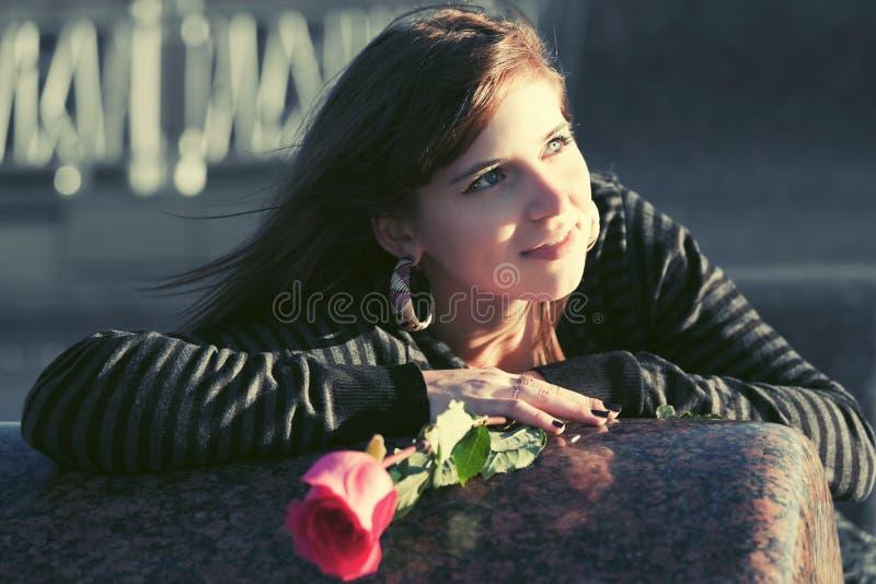 De gelukkige jonge vrouw met een rood nam openlucht toe stock afbeelding