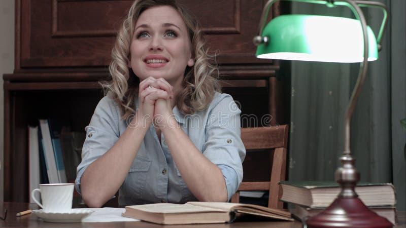 De gelukkige jonge vrouw met handen clasped het bidden terwijl het zitten bij bureau in haar huisbureau royalty-vrije stock fotografie