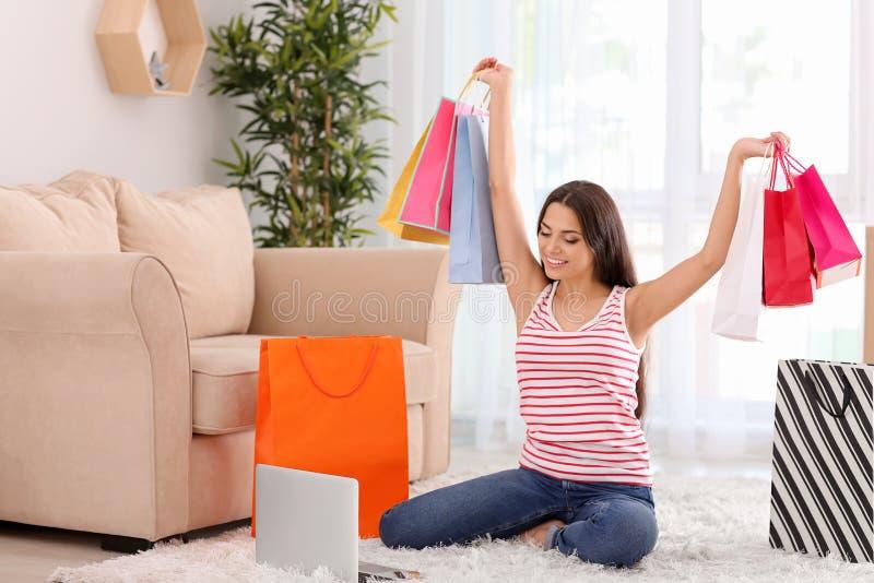De gelukkige jonge vrouw met het winkelen doet thuis in zakken royalty-vrije stock foto's